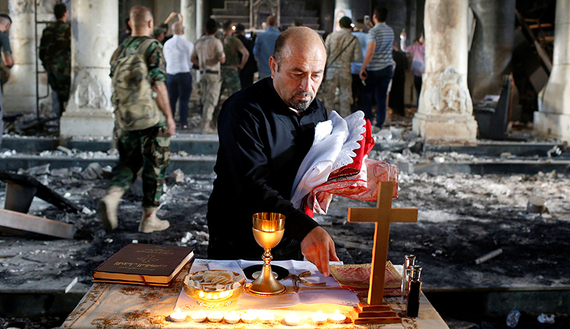 An Iraqi Christian prepares for the first Sunday mass at the Grand Immaculate Church since it was recaptured from Islamic State in Qaraqosh